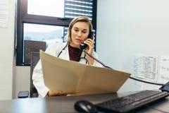 Praticien de médecine examinant des rapports médicaux et parlant sur p Photo stock