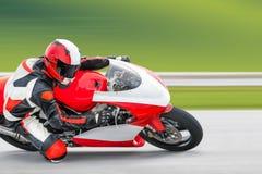 Pratique en matière de moto se penchant dans un coin rapide sur la voie photo stock