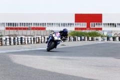 Pratique en matière de moto se penchant dans un coin rapide sur la voie image stock