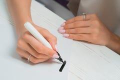 Pratiques en matière d'étudiant de calligraphe par écrit avec le marqueur noir sur la toile Indépendant créatif d'artiste travail images libres de droits