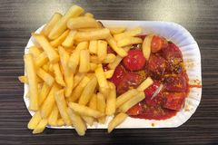 Prato alemão de Currywurst da salsicha cortada com molho e batatas fritas de caril fotografia de stock