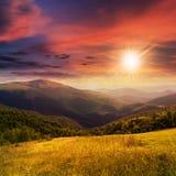 Prato in alte montagne al tramonto Immagine Stock