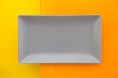 Prato cerâmico cinzento vazio sobre sobre a tabela de madeira alaranjada e amarela imagem de stock royalty free