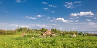 prato collinoso di estate invaso con erba spessa con le grandi pietre sotto il cielo nuvoloso blu fotografie stock libere da diritti