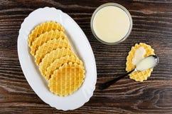 Prato com cookies, leite condensado na colher na cookie, bacia com leite condensado na tabela de madeira Vista superior imagens de stock