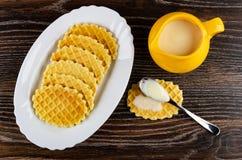 Prato com cookies, leite condensado na colher na cookie, jarro com leite condensado na tabela de madeira Vista superior fotografia de stock royalty free