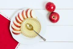 Prato com maçãs, mel e uma colher no fundo de madeira branco Ano novo judaico, Rosh Hashanah, wiev superior Fotos de Stock Royalty Free
