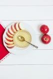Prato com maçãs, mel e uma colher no fundo de madeira branco Ano novo judaico, Rosh Hashanah, wiev superior Imagem de Stock