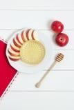 Prato com maçãs, mel e uma colher para o mel no fundo de madeira branco Ano novo judaico, Rosh Hashanah, wiev superior Imagens de Stock Royalty Free