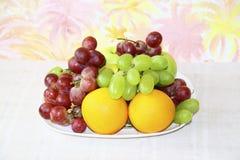 Prato com maçãs, uvas e laranjas Foto de Stock Royalty Free