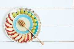 Prato com mel, maçãs e uva no fundo de madeira branco Ano novo judaico, Rosh Hashana, vista superior Foto de Stock Royalty Free
