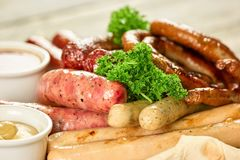 Prato com seis tipos das salsichas na placa de madeira, close up Fotografia de Stock Royalty Free