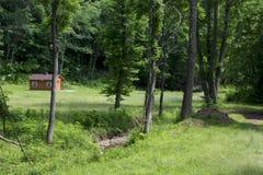 Prato con la piccoli cabina e corso d'acqua Fotografie Stock