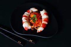Prato culinário original de cenouras e dos pescoços conservados deliciosos do camarão no prato cerâmico preto com as varas de bam imagem de stock