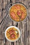 Prato da couve cozinhado com os reforços de carne de porco fumado em Saucepot de aço inoxidável servido na tabela de piquenique r Foto de Stock Royalty Free