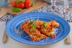 Prato da massa do cannelloni com molho do tomatoe em uma placa azul com a Imagem de Stock Royalty Free