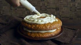 Prato da sobremesa do cozimento Creme de derramamento do cozinheiro chefe no bolo de cenoura Fazendo a torta da cenoura vídeos de arquivo
