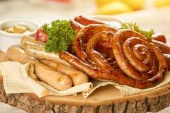 Prato da variedade da salsicha na placa de madeira redonda Imagens de Stock Royalty Free