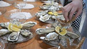 Prato das ostras antes de servir convidados no restaurante Uma grande placa no gelo junto com um limão Close-up, cozinha video estoque