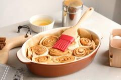 Prato de cozimento com rolos de canela e a escova de pastelaria crus imagens de stock