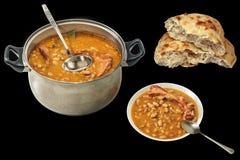 Prato de feijões cozidos com os reforços de carne de porco fumado e o naco rasgado pão de Pitta isolados no fundo preto Imagem de Stock