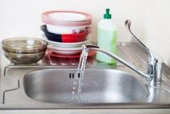 Prato de lavagem da esponja da banca da cozinha do dishware da limpeza Feche acima das mãos fêmeas no lavagem de borracha proteto Imagem de Stock Royalty Free