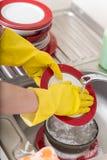 Prato de lavagem da esponja da banca da cozinha do dishware da limpeza Feche acima das mãos fêmeas no lavagem de borracha proteto Imagens de Stock