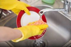 Prato de lavagem da esponja da banca da cozinha do dishware da limpeza Feche acima das mãos fêmeas no lavagem de borracha proteto Imagens de Stock Royalty Free