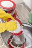 Prato de lavagem da esponja da banca da cozinha do dishware da limpeza Feche acima das mãos fêmeas no lavagem de borracha proteto Imagem de Stock