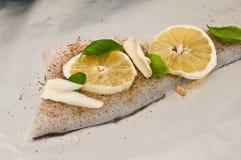 Prato de peixes do bacalhau com limões e tomates Foto de Stock