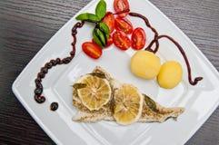 Prato de peixes do bacalhau com limões e tomates Imagens de Stock