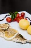 Prato de peixes do bacalhau com limões e tomates Imagem de Stock Royalty Free