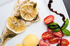 Prato de peixes do bacalhau com limões e tomates Fotos de Stock Royalty Free