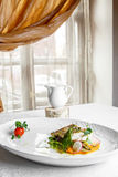 Prato de peixes - faixa do zander na placa na tabela perto da janela fotografia de stock royalty free