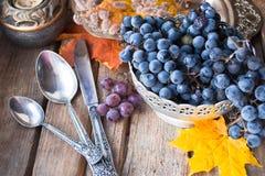 Prato de prata velho com uvas, colheres, folhas de outono no fundo de madeira foto de stock