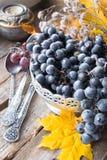 Prato de prata velho com uvas, colheres, folhas de outono no fundo de madeira imagens de stock royalty free