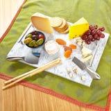 Prato de serviço de mármore com queijo e biscoitos e aperitivos Fotos de Stock Royalty Free