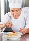 Prato de Sprinkling Spices On do cozinheiro chefe Fotografia de Stock