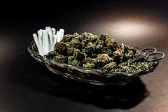 Prato de vidro elegante com botão da marijuana, tesouras e dúzia junções foto de stock