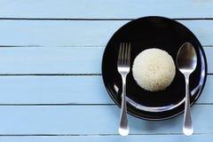 Prato do arroz com a colher com forquilha e espaço no fundo azul, vista superior Fotos de Stock Royalty Free