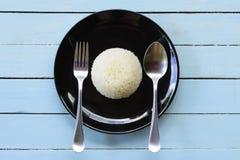 Prato do arroz com a colher com a forquilha no fundo azul, vista superior Foto de Stock
