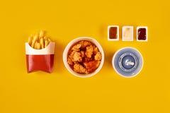 Prato do fast food no fundo amarelo Frango frito e batatas fritas ajustados do fast food Leve embora o fast food imagens de stock royalty free