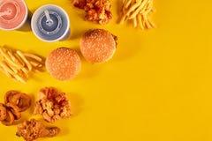 Prato do fast food no fundo amarelo Frango frito do fast food, hamburguer da carne e batatas fritas ajustados Leve embora o fast  fotografia de stock royalty free