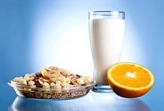 Prato do muesli, do leite de vidro e parcialmente da laranja Fotos de Stock