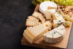 Prato do queijo do gosto em uma placa de madeira Alimento para o vinho e romântico, guloseimas do queijo em uma tabela de pedra e Imagens de Stock Royalty Free