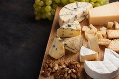 Prato do queijo do gosto em uma placa de madeira Alimento para o vinho e romântico, guloseimas do queijo em uma tabela de pedra e Fotos de Stock Royalty Free