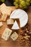 Prato do queijo do gosto em uma placa de madeira Alimento para o vinho e romântico, guloseimas do queijo em uma tabela de pedra e Fotografia de Stock Royalty Free