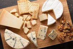 Prato do queijo do gosto em uma placa de madeira Alimento para o vinho e romântico, guloseimas do queijo em uma tabela de pedra e Foto de Stock