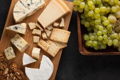 Prato do queijo do gosto em uma placa de madeira Alimento para o vinho e romântico, guloseimas do queijo em uma tabela de pedra e Fotos de Stock