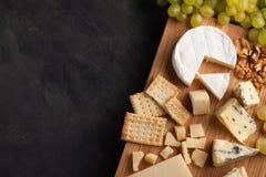 Prato do queijo do gosto em uma placa de madeira Alimento para o vinho e romântico, guloseimas do queijo em uma tabela de pedra e Foto de Stock Royalty Free